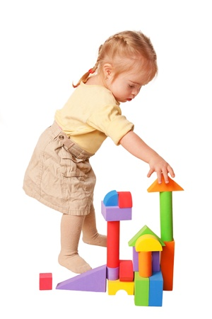Baby girl building from toy blocks. Isolated on white background photo