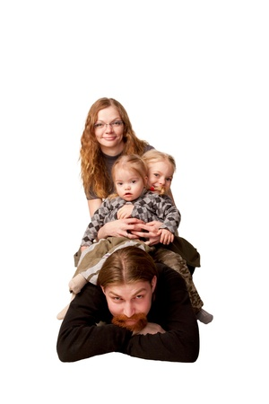 Happy redhead family, father, mother and two children smiling and forming a tower photo