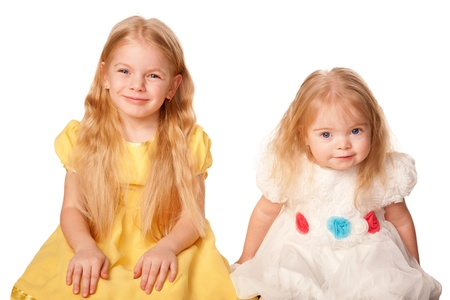 Two lovely sisters. Preschooler and baby girl. Isolated on white background. photo