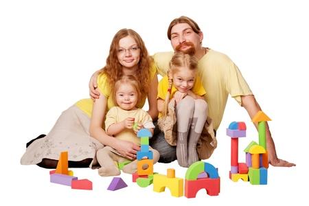 Gelukkig roodharige vader, moeder en twee kinderen bouwen van speelgoed blokken. Family concept. Geà ¯ soleerd op witte achtergrond