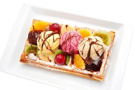 Belgian waffle with fruit, ice cream, chocolate.  Isolated on white background photo