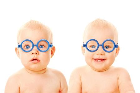 niñas gemelas: Dos bebés gemelos varones con gafas. Un chico serio, el otro niño sonriendo. Los jóvenes estudiantes. Aislado sobre fondo blanco