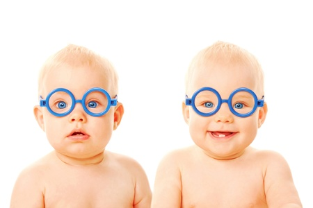 good boy: Two twins babies boys wearing glasses. One kid serious, the other child smiling. Young students. Isolated on white background Stock Photo