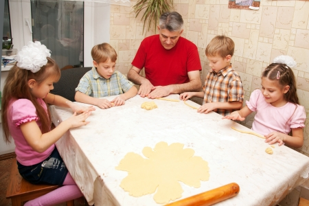 little dough: Happy big family cooking a pie together. Father and four children, two boys and two girls playing with dough in the kitchen. Stock Photo