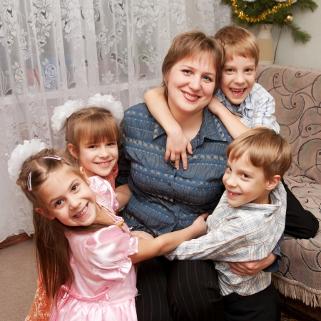 Four children hugging mother. Family and love concept. photo
