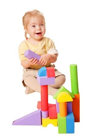 Baby meisje gebouw uit speelgoed blokken. Geà ¯ soleerd op witte achtergrond Stockfoto