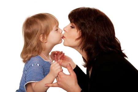 Baby daughter and mother kissing. Side view.  Isolated on white background photo