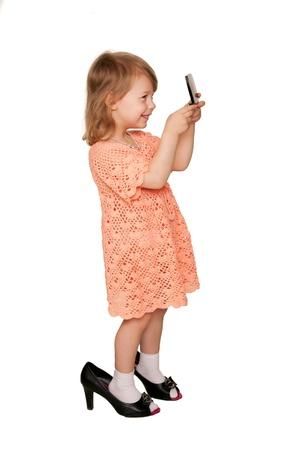 jolie petite fille: Petite fille regardant dans le miroir. Vue de c�t�. Un enfant portant des chaussures de sa m�re. Isol� sur fond blanc Banque d'images