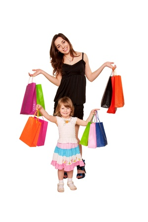 Family shopping. Two sisters, a teenager and a little girl holding up shopping bags and smiling. Holidays and gifts concept. Isolated on white background photo