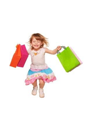 Bonne petite fille courir et sauter avec des sacs. Isolé sur fond blanc