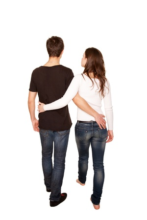 Teenagers in love, boy and girl hugging and walking. Rear view. Isolated on white background