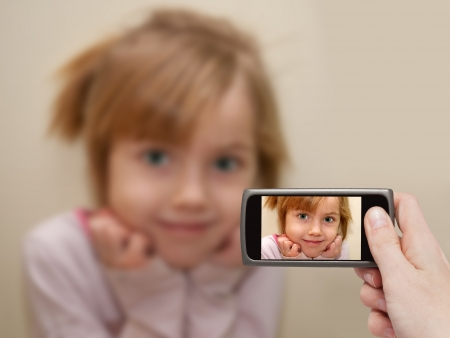 Man's hand making photo of a little girl with a mobile phone. Selective focus on a mobile phone with a portrait of a girl.