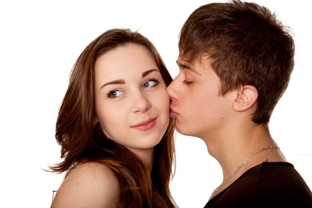 Loving couple teenagers. Boy kissing a girl. Isolated on white background photo