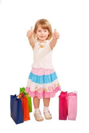 ok symbol: Piccola acquirente bambina con borse della spesa che mostra un pollice in alto o simbolo OK. Riuscito concetto di shopping. Isolato su sfondo bianco Archivio Fotografico