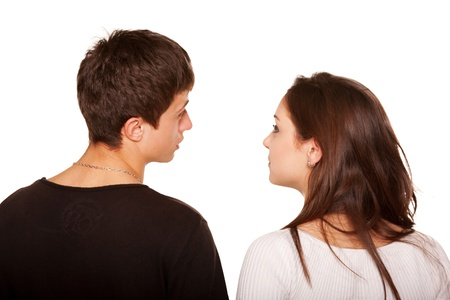 Teens couple, boyfriend and girlfriend, looking at something and talking. Rear view. Isolated on white background photo