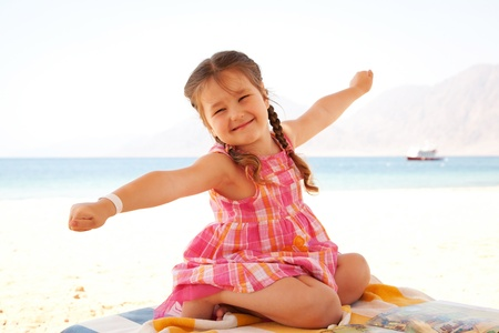 Happy little girl on the beach raising hands up and sitting on a lounger. Summer holidays.
