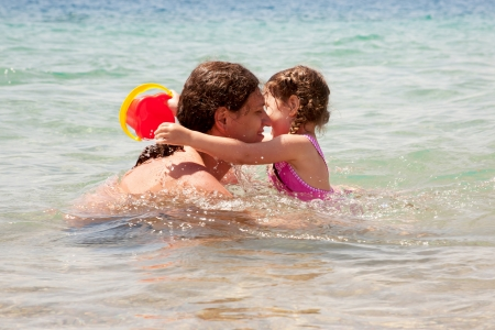 Father and baby daughter playing in the water. Summer holidays. photo