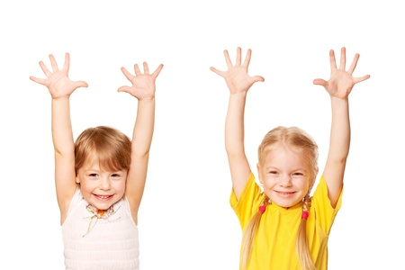 Two little girls raising their hands up. Young students or helpers. Isolated on white background Stock Photo