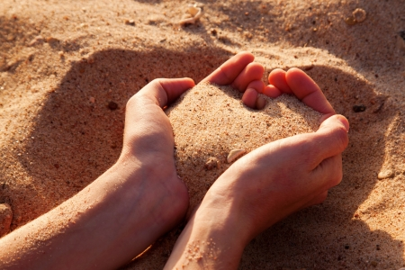 Two hands forming heart from sand  Summer holidays  photo