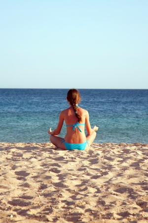 Young woman meditating on the beach. Rear view. Summer holiday photo