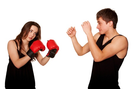 hassle: Teenagers boy and girl quarreling, gesticulating and shouting at each other. The girl wore a pair of boxing gloves and beating the guy, the guy defending himself. Isolated on white background Stock Photo
