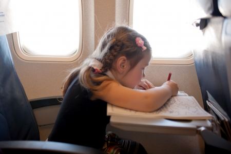Little girl drawing while flying by plane