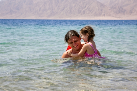 Father and baby daughter playing in the water photo