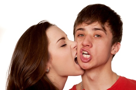 Girl biting guy on the cheek Isolated on white background photo