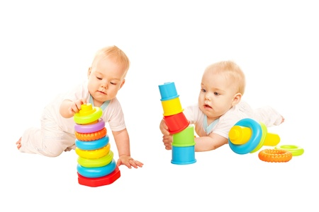 Two baby playing with colorful toys. Isolated on white background. photo