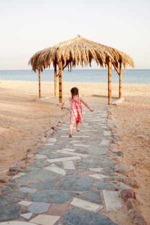 Little girl running to the sea. Rear view. Summer holidays. photo