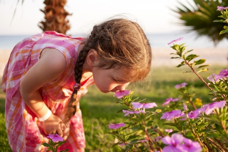 field study: Little girl smelling flowers on the beach. Summer holidays.
