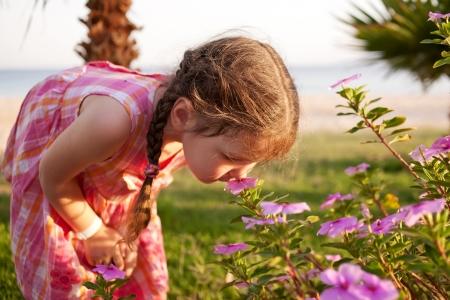 Pequeñas flores huelen de la chica en la playa. Vacaciones de verano.