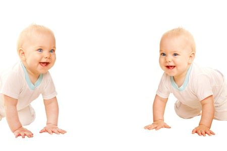 Two twins babies crawling, peering and laughing.  Isolated on white background.