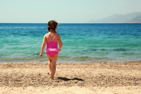 little girl beach: Little girl standing on beach in swimsuit and going to swim in the sea. Rear view. Summer holidays.