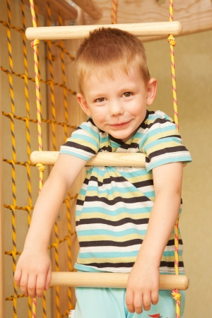 rope ladder: Little child playing sports at sport center  Kid climbing on a rope ladder
