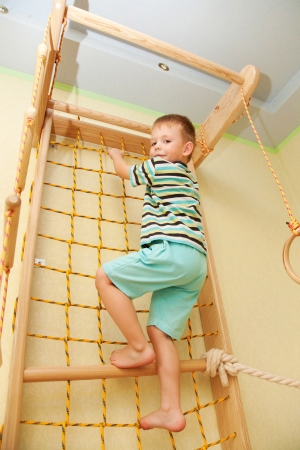 Kid climbing on a rope net photo