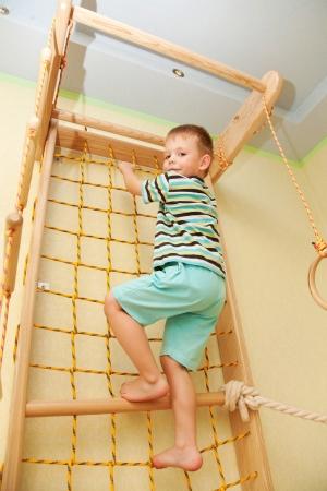 hermanos jugando: Kid sube en una red de cuerda Foto de archivo