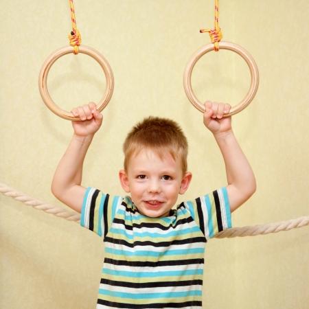 Kid exercising on gymnastic rings photo