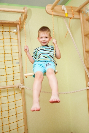 Little boy playing sports, swinging on a swing in his room  photo