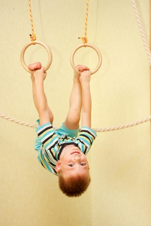 Little boy playing sports at sport center  Kid exercising on gymnastic rings photo