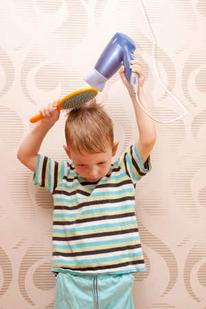 The little boy drying hair with  hair dryer Stock Photo - 20408670