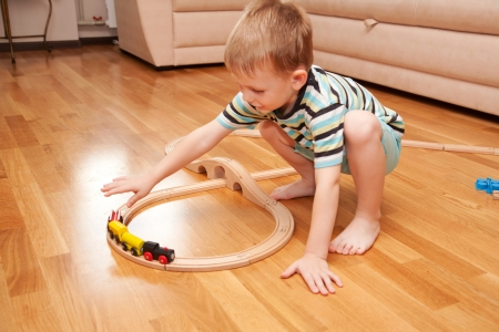 wood railroad: Little boy playing with wooden railway on the floor