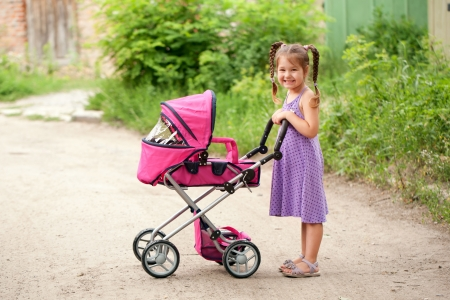 Little girl walking with a toy stroller. Little Mama. Stock Photo