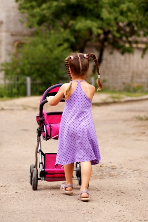 baby doll: Little girl walking with a toy stroller. Little Mama. Stock Photo