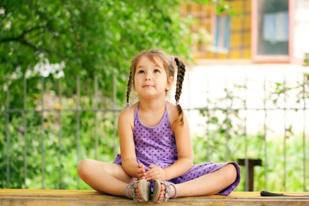 little girl sitting: Little girl meditating outdoors. Relaxation and recreation.