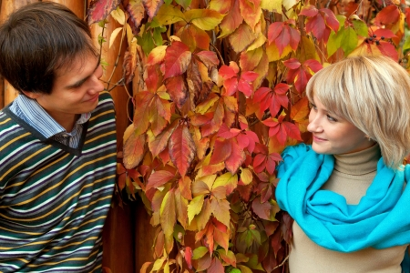 Young couple in love in the autumn forest. Man and woman looking to one another face to face, eye to eye. photo