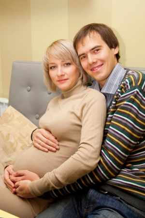 Beautiful pregnant couple in love sitting on the sofa and hugging photo