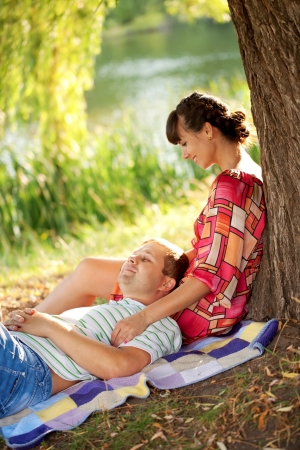 Happy middle-aged couple relaxing near the river  in the sunlight at sunset  Man sleeping woman looking at him with love  Summer holiday  photo
