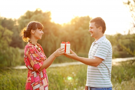 Middle-aged couple in love outdoors in the sunlight at sunset   Man giving to his woman a gift  Happy family concept  photo