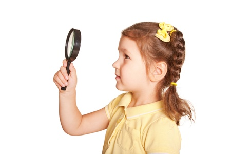 Little girl looking through a magnifying glass carefully. Side view. Isolated on white background photo